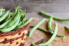 Raw green beans in a brown basket and on a burlap textile. Fresh young beans pods. Old wooden background. Green string beans. Raw green string beans. Fresh green Royalty Free Stock Image