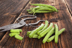 Raw green beans. Raw fresh green beans with water drops on brown wooden textured table. Fresh vegetable eating Royalty Free Stock Image