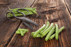 Raw green beans. Raw fresh green beans with water drops on brown wooden textured table. Fresh vegetable eating Royalty Free Stock Photo