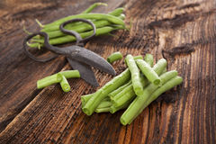 Raw green beans. Raw fresh green beans with water drops on brown wooden textured table. Fresh vegetable eating Stock Photography