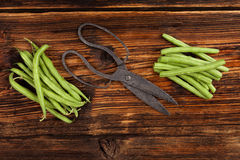 Raw green beans. Raw fresh green beans with water drops on brown wooden textured table. Fresh vegetable eating Stock Images