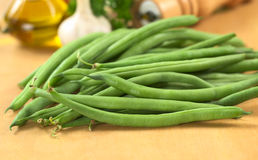 Raw Green Beans. Fresh raw green beans on wooden board with oil, garlic, parsley and pepper mill in the back (Selective Focus, Focus on the bean in the front Royalty Free Stock Photography