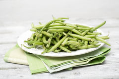 Raw green beans (Phaseolus vulgaris) on plate Royalty Free Stock Images