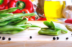 Raw green beans prepared for cooking. On a wood cutting board on a kitchen with vegetables background Stock Photos
