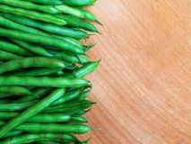 Raw green beans on wood background, close up, top view, copyspace. Pods of green raw beans top view on wooden surface, text space. Flat lay. Healthy eatinfg stock photo