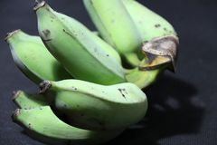 Raw and green cultivated banana put on the black floor. it is a long curved fruit that grows in clusters. Raw and green cultivated banana put on the black floor Royalty Free Stock Images
