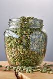 Raw green peas in glass jar on a log over grey blurred background, close-up, selective focus. Some copy space for your inscription. Studio shot. Organic Royalty Free Stock Photo