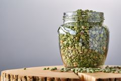 Raw green peas in glass jar on a log over grey blurred background, close-up, selective focus. Some copy space for your inscription. Studio shot. Organic Royalty Free Stock Images