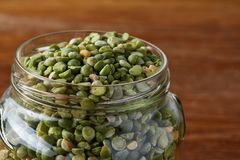Raw green peas in glass jar over wooden background, close-up, selective focus. Some copy space for your inscription. Organic protein. Perfect ingredient for royalty free stock photo