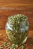 Raw green peas in glass jar over wooden background, close-up, selective focus. Some copy space for your inscription. Organic protein. Perfect ingredient for royalty free stock photography