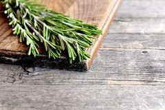 Raw green rosemary sprigs on a kitchen board and an old wooden background with empty space for text. Aromatic herb used in cooking, medicine, cosmetics. Closeup Stock Photography