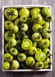 Raw green tomatoes in wooden box. Selective focus Royalty Free Stock Photos