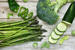 Raw green vegetables on a rustic white table. High-angle shot of some different raw green vegetables, such as green pepper, asparagus, broccoli or zucchini, on a Royalty Free Stock Image