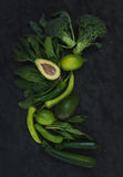 Raw green vegetables set. Broccoli, avocado, pepper, spinach, zuccini and  lime on  dark stone background Royalty Free Stock Image