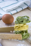 Raw green and yellow pasta with egg and white towel on table. Raw green and yellow pasta with egg and white towel on wooden table Stock Photos