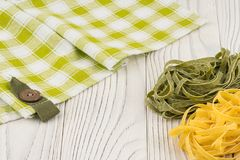 Raw green and yellow pasta on an old white wooden table. stock photo