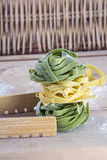 Raw green and yellow pasta on table with wicker background. Raw green and yellow pasta on wooden table with wicker background Stock Photo