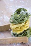 Raw green and yellow pasta on table. Raw green and yellow pasta on wooden table Stock Photography