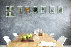 Raw grey wall. Framed leaves hanging on the raw grey wall in stylish dining room stock photos