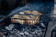 Raw Grilled chicken Leg on grill, over coals with smoke Stock Image