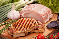 Raw and grilled meat  with vegetables. On a  wooden board Stock Photography