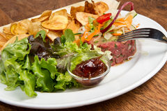 Raw ground beef. With chips and salad Stock Image
