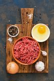 Raw ground beef in a bowl on a cutting board with spices on a dark rustic background. Ingredients for cooking cutlets, meatballs. View from above Royalty Free Stock Image