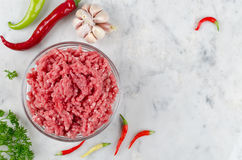 Raw ground beef and ingredients. Raw ground beef, hot peppers and garlic  on white marble background Stock Photos