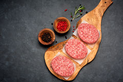 Raw Ground Beef Meat Burger cutlets. Raw Ground Beef Meat Burger cutlets on black background. Top view Stock Photo