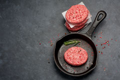 Raw Ground Beef Meat Burger cutlets  in cast iron pan. Top view. Raw Ground Beef Meat Burger cutlets on black background. Top view Stock Images