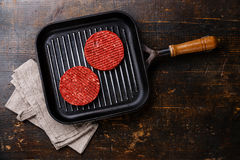 Raw Ground beef meat Burger cutlets on pan. Raw Ground beef meat Burger steak cutlets on frying pan on wooden background Royalty Free Stock Photos