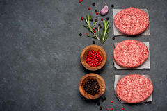 Raw Ground Beef Meat Burger cutlets. Top view. Raw Ground Beef Meat Burger cutlets on black background. Top view Royalty Free Stock Images