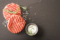 Raw Ground beef meat Burger steak cutlets. On a black background stone Stock Image