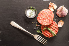 Raw Ground beef meat Burger steak cutlets. On a black background stone Stock Photos