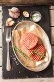 Raw Ground beef meat Burger steak cutlets. On a black background stone Royalty Free Stock Image