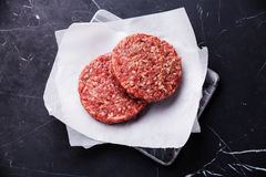 Raw Ground beef meat Burger steak cutlets. On dark marble background Royalty Free Stock Images