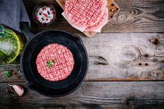 Raw ground beef meat burger steak cutlets in frying pan Stock Photo