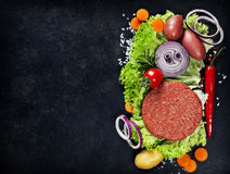 Raw Ground beef meat Burger steak cutlets with seasoning and veg. Etables on vintage  board Royalty Free Stock Photos