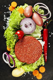 Raw Ground beef meat Burger steak cutlets with seasoning and veg. Etables on vintage  board Royalty Free Stock Image