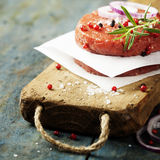Raw Ground beef meat Burger steak cutlets with seasoning. On vintage wooden boards Stock Photography
