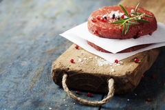 Raw Ground beef meat Burger steak cutlets with seasoning. On vintage wooden boards Royalty Free Stock Photo