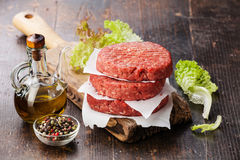 Raw Ground beef meat Burger steak cutlets. And seasonings on dark wooden background stock photo