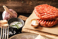 Raw Ground beef meat Burger steak cutlets. On  wooden background Royalty Free Stock Images