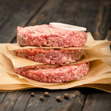 Raw ground beef meat cutlets close up. Close up raw ground beef meat cutlets on wooden table Royalty Free Stock Photo