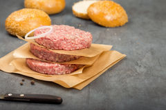 Raw ground beef meat cutlets on paper. Close up Stock Photos