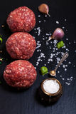Raw ground beef meat steak cutlets with herbs and spices on blac. K table or board for background. Selective focus Royalty Free Stock Photography