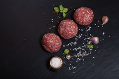 Raw ground beef meat steak cutlets with herbs and spices on blac. K table or board for background. Selective focus Stock Images