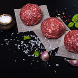 Raw ground beef meat steak cutlets with herbs and spices on blac. K table or board for background. Selective focus Royalty Free Stock Photo