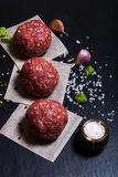 Raw ground beef meat steak cutlets with herbs and spices on blac. K table or board for background. Selective focus Royalty Free Stock Image