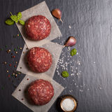Raw ground beef meat steak cutlets with herbs and spices on blac. K table or board for background. Selective focus Stock Photos
